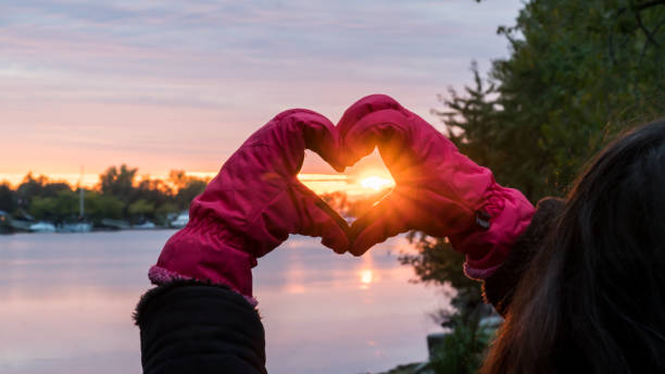 Hands Making Heart Shape around beautiful Sunset wearing Pink gloves - Winter Solstice Love Landscape over water stock photo