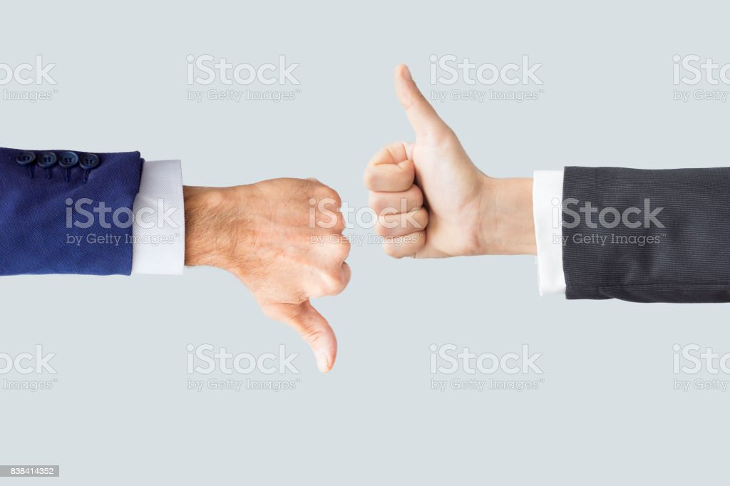 Hands making thumbs up and down stock photo