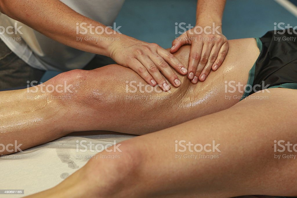 hands massaging athlete's thigh after running - Royalty-free Active Lifestyle Stock Photo