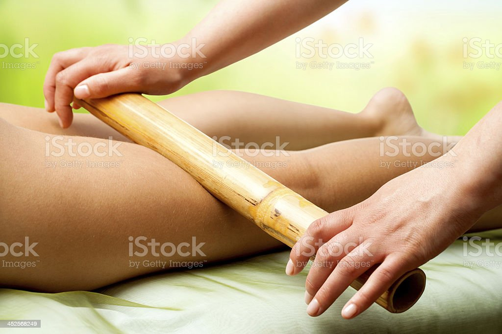 Hände massieren weibliche Beine mit Bambus. – Foto