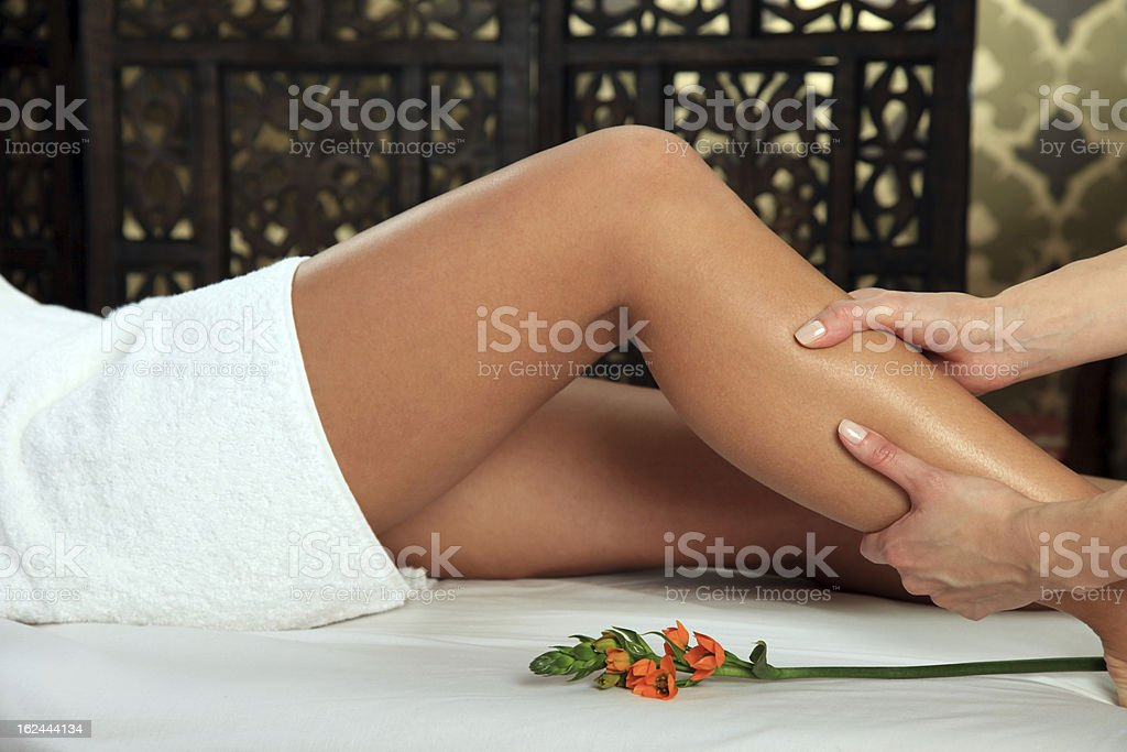 Hands massaging young woman's legs in parlor with flower stock photo