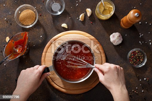 istock Hands mix the bbq sauce with the whisk in the saucepan. 936987796