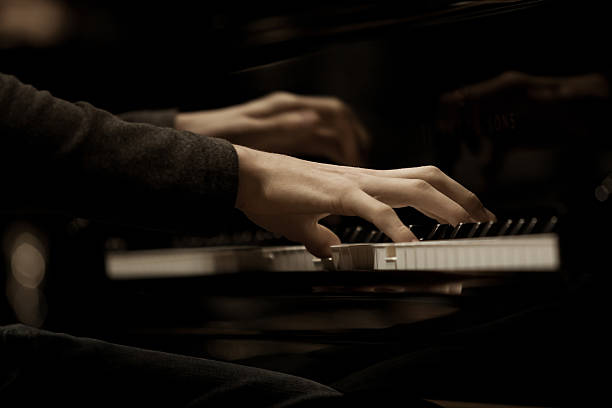 Hands musician playing the piano Hands musician playing the piano closeup in dark colors pianist stock pictures, royalty-free photos & images