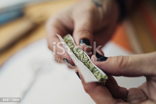 istock Hands of a 40 year old woman rolling a joint, prescribed by a doctor for her chronic illness. 848773634