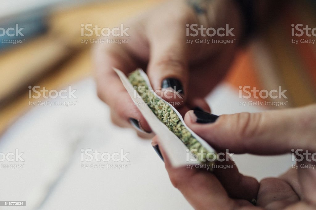 Hands of a 40 year old woman rolling a joint, prescribed by a doctor for her chronic illness. stock photo