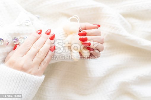 946930880istockphoto Hands of a beautiful well-groomed woman with red nails on a white background. Nail polishing in white. 1173623050
