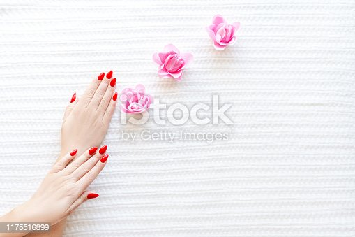 946930880istockphoto Hands of a beautiful well-groomed woman with red nails on a white background. Nail polishing in white. 1175516899