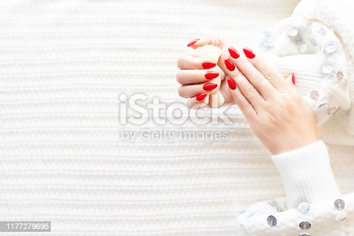946930880istockphoto Hands of a beautiful well-groomed woman with red nails on a white background. Nail polishing in white. 1177279695