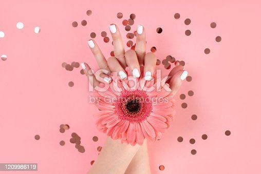 946930880 istock photo Hands of a beautiful woman on a colorful background. Delicate palm with natural manicure, clean skin. Light pink nails. 1209986119
