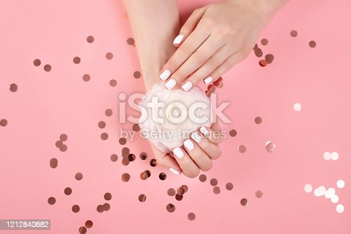946930880 istock photo Hands of a beautiful woman on a colorful background. Delicate palm with natural manicure, clean skin. Light pink nails. 1212840882