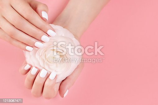 946930880 istock photo Hands of a beautiful woman on a colorful background. Delicate palm with natural manicure, clean skin. Light pink nails. 1213087471