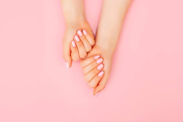 mãos de uma mulher bonita em um fundo cor-de-rosa. - manicure - fotografias e filmes do acervo