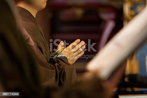 Close up of a young Buddhist Monks hands holding prayer beads while he prays