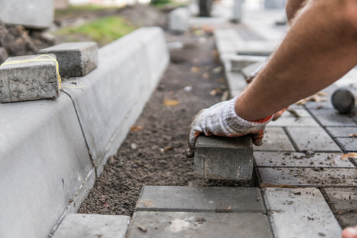 Hands of a builder in his orange gloved hands with a hammer fitting laying new exterior paving stones carefully placing one in position on a leveled and raked soil base. Sand foundation. Building