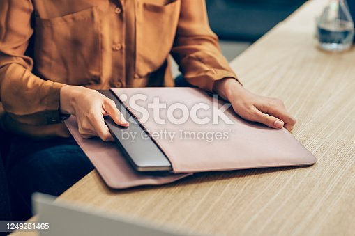 Unrecognizable woman in a yellow shirt taking her laptop pc out of the bag at work.