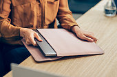 istock Hands of a Businesswoman Taking Out her Laptop Computer out of the Sleeve on her Desk 1249281465