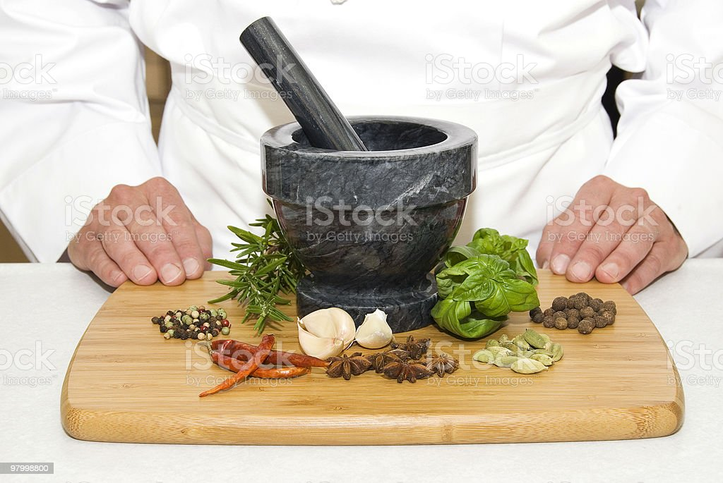 Hands of a chef with herbs, pestle, mortar royalty-free stock photo