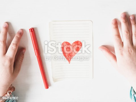 Hands of a child, a pencil, a sheet of paper with a drawn heart on a white background top view. Congratulations to my beloved parents. Happy family concept
