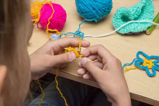 Hands of a child are embroidered with threads using a hook
