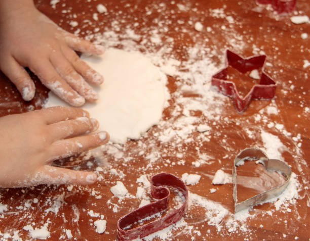 hands of a child preparing salt dough for Christmas decorations stock photo