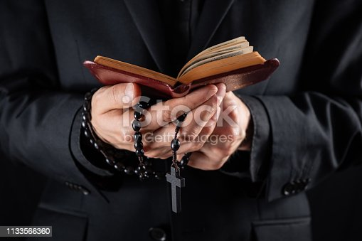 istock Hands of a christian priest dressed in black holding a crucifix and reading New Testament book. 1133566360