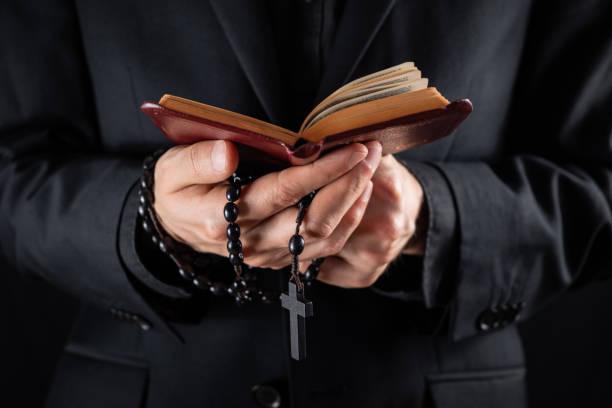 十字架を持ち、新約聖書の本を読む、黒い服を着たクリスチャンの司祭の手。 - 懺悔 ストックフォトと画像