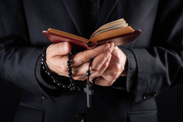 Hands of a christian priest dressed in black holding a crucifix and reading New Testament book. Religious person studies Bible and holds prayer beads, low-key image clergy stock pictures, royalty-free photos & images