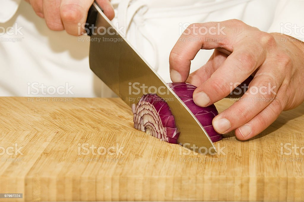 Hands of a cook cutting onion in the kitchen royalty-free stock photo