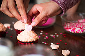 Hands of a couple decorating cupcakes for valentine's day