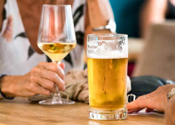 Hands of a couple having beer and white wine sitting in a table outdoors a bar in Spli, Croatia. stock photo