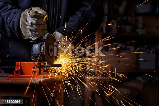 Hands of a craftsman with working gloves cutting an iron bar with the electric angle grinder which sprays many hot sparks in the dark workshop, dangerous work, copy space