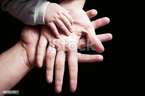 Hands of a family on black background. Mother, father and child..