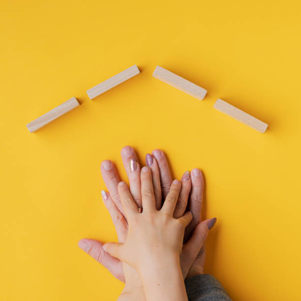 Hands of a father, mother and child stacked on yellow background stock photo