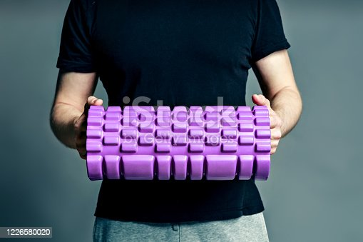 Hands of a fitness trainer man holding a roller for myofascial relaxation on a gray background.