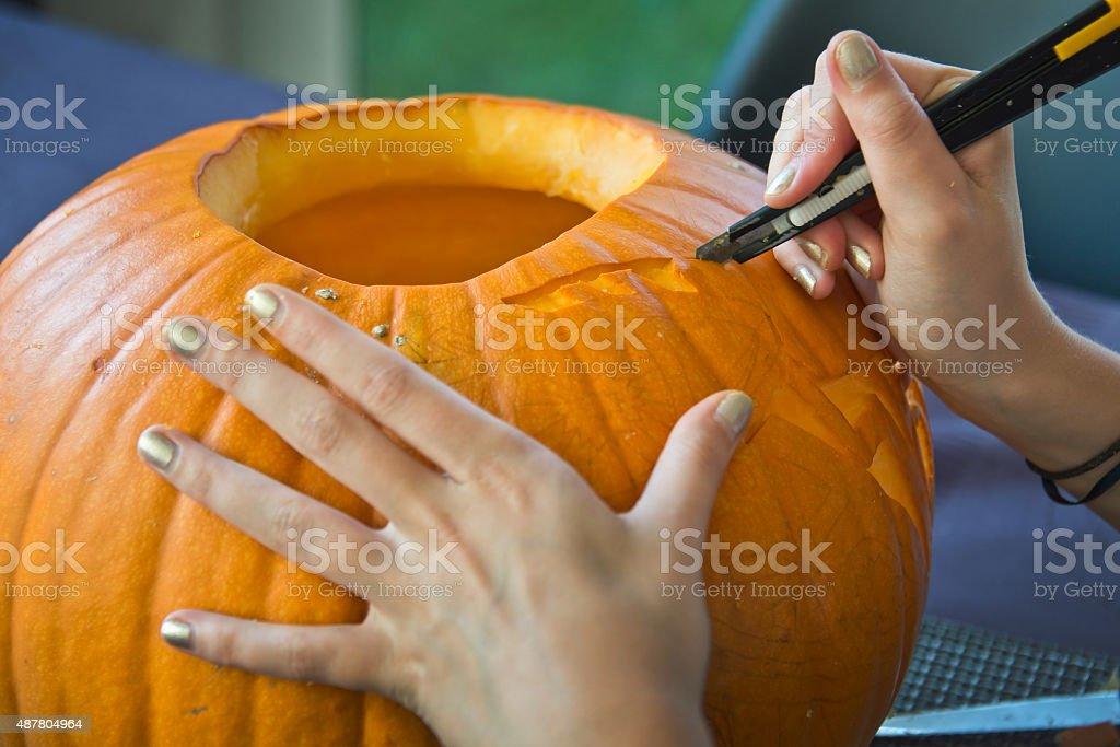 Hands of a girl carving a Halloween pumpkin stock photo