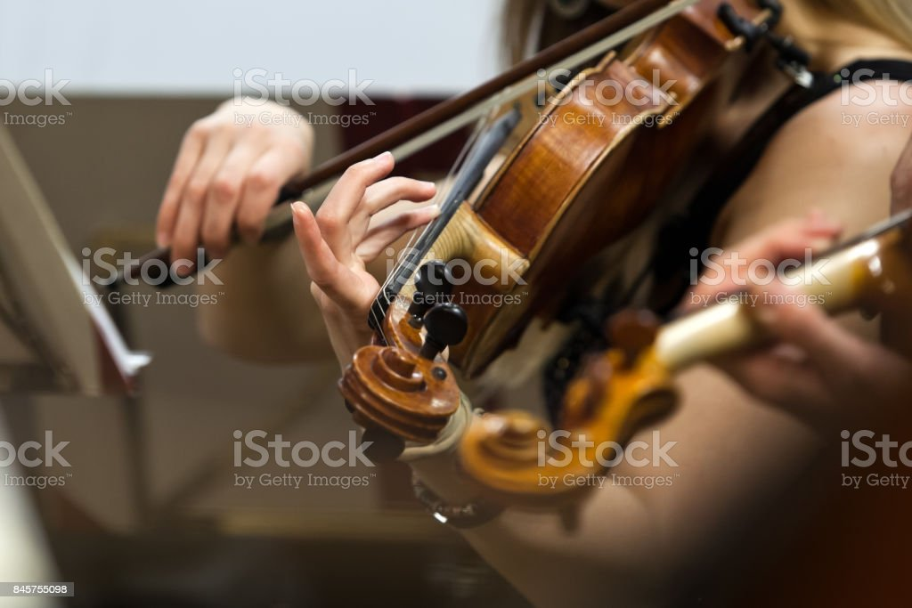 Hands of a girl playing the violin stock photo
