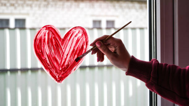 hands of a girl with a paintbrush painting red heart on a window, copy space for text, stay home stock photo