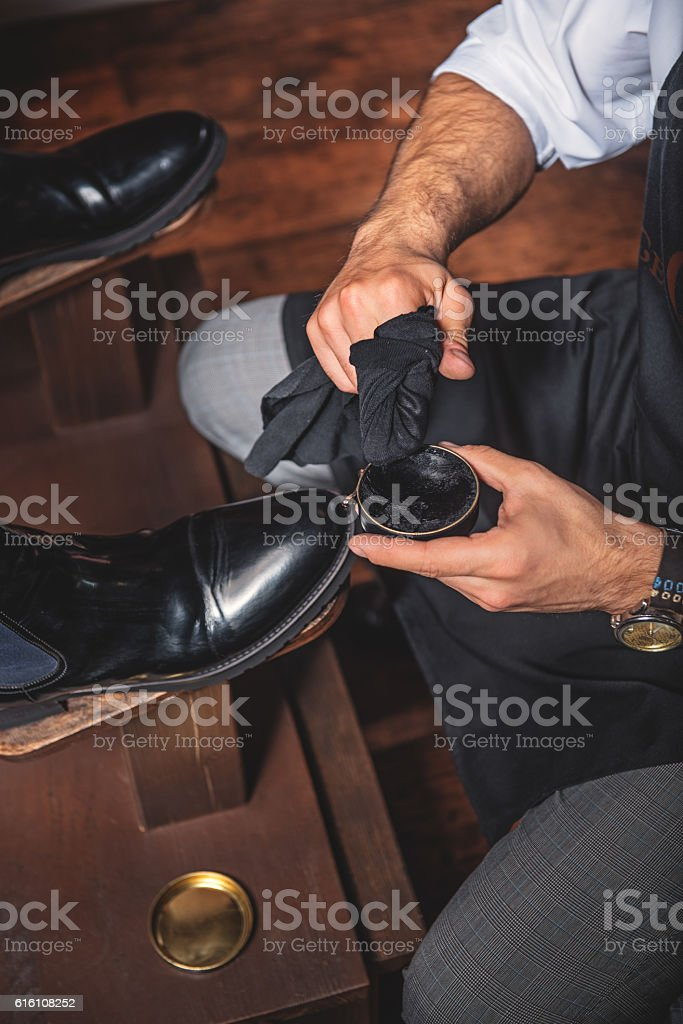 hands of a guy polishing the shoes stock photo
