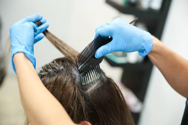 手袋の中の美容師の手は染毛をする - 美容室 ストックフォトと画像