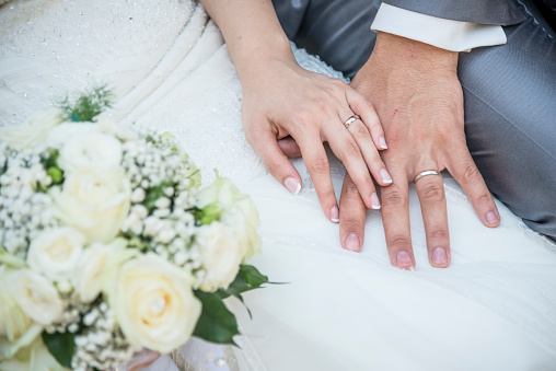 hands of a just married couple with the wedding rings and bouquet