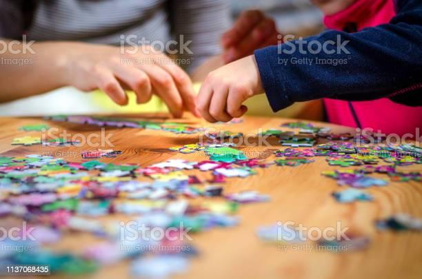 Hands of a little child and parent plying jigsaw puzzle game on a picture id1137068435?b=1&k=6&m=1137068435&s=612x612&h=k inqpnhwznyfj cfapbrmv7k9myaag3c3b s2kz2vs=