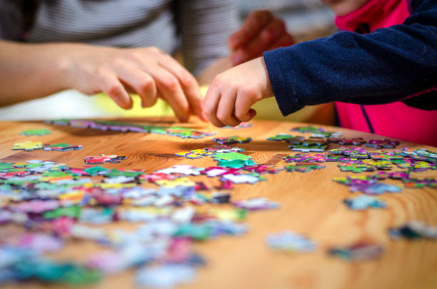 hands of a little child and parent plying jigsaw puzzle game on a wooden table - puzzle foto e immagini stock
