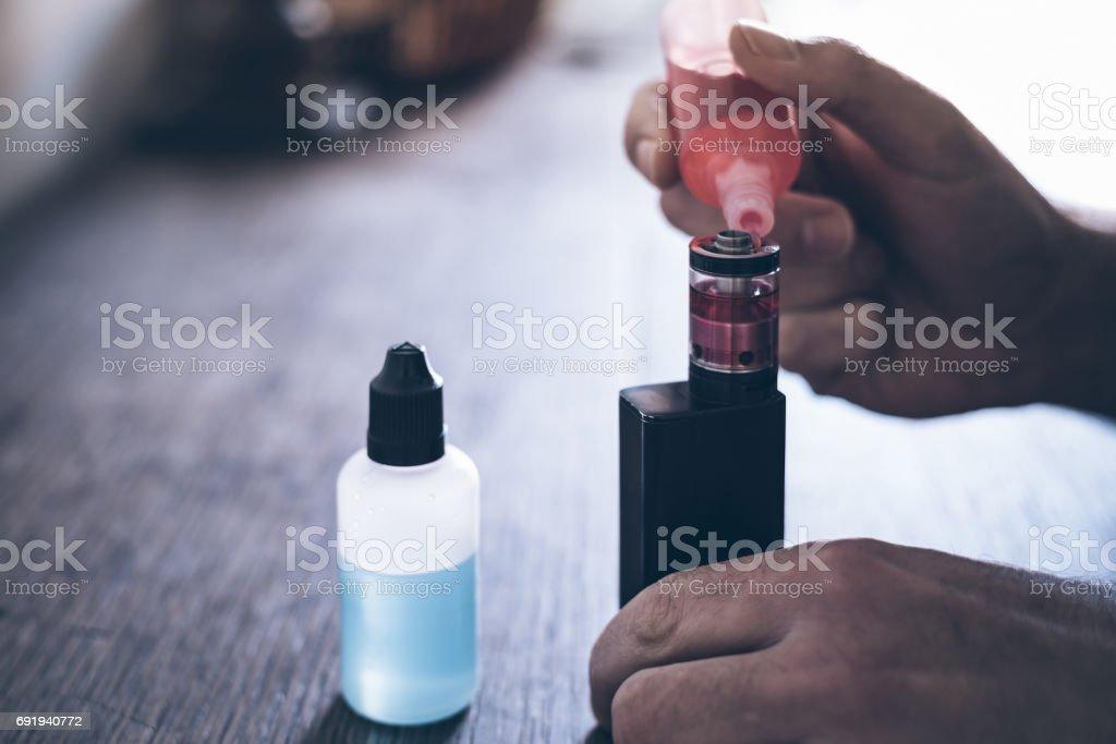 Händen der eine männliche Person, die den Tank einer e-Zigarette mit roter Flüssigkeit nachfüllen – Foto