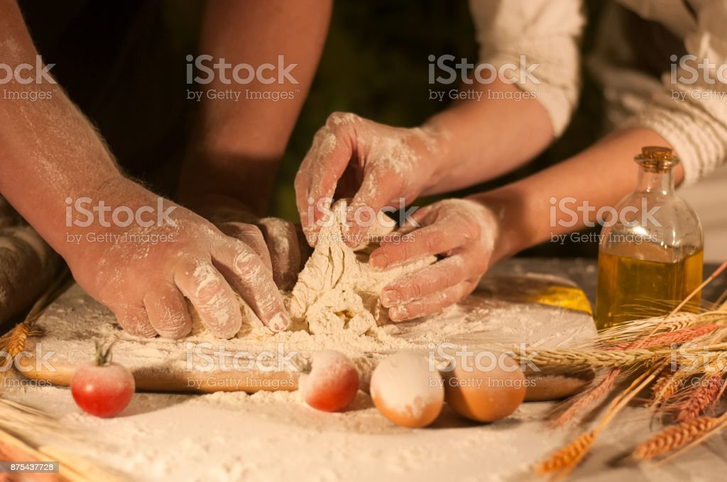 hands of a man and a woman dough flour family stock photo
