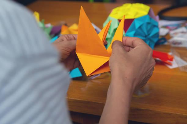 hände eines mannes eine farbigen origami-papier zu schaffen. kreativität - origami anleitungen stock-fotos und bilder