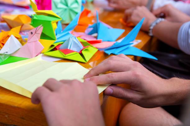 hände eines mannes, der ein farbiges origami-papier schafft. schöpferische begabung - origami anleitungen stock-fotos und bilder