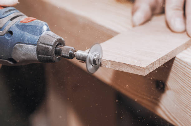 hands of a man holding a dremel tool with an installed small circular saw. wood processing. workshop. manufacture of wooden products. joiner's cutting tool - dremel wood stock photos and pictures