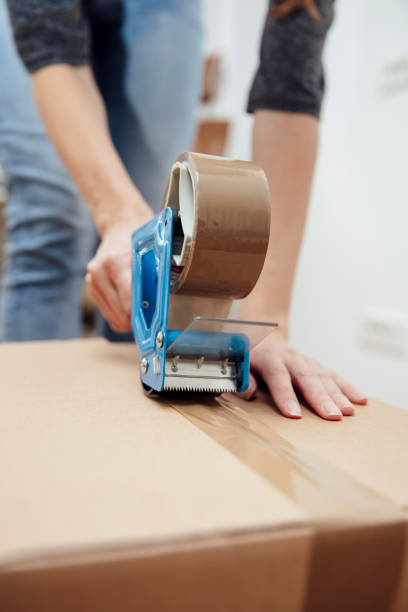 Hands of a man using a tape dispenser to seal a shipping box stock photo