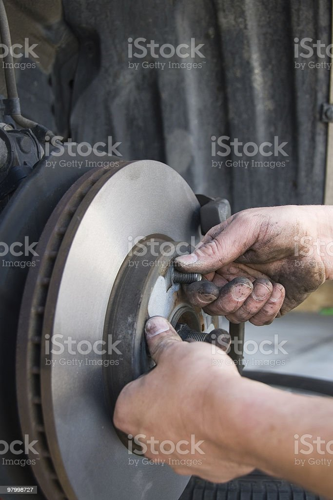Hands of a mechanic changing brakes royalty-free stock photo