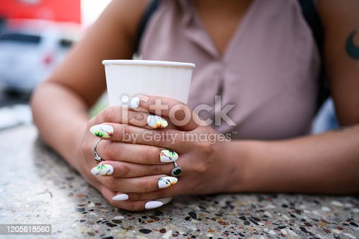 This is a photograph of the hands of a self identifying Mixed Race woman who is holding a paper cup of water while sitting at an outdoor cafe in Wynwood, Miami.